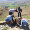 Young Ranger Tom Blackburn with other volunteers clearing drains on the paths up to Blencathra
