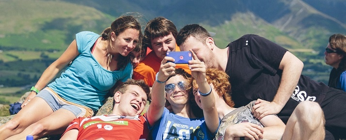 Group of young people taking a photo on top of a hill on a sunny day