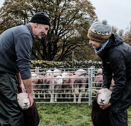 Andrea Meanwell and a farmer with sheep.