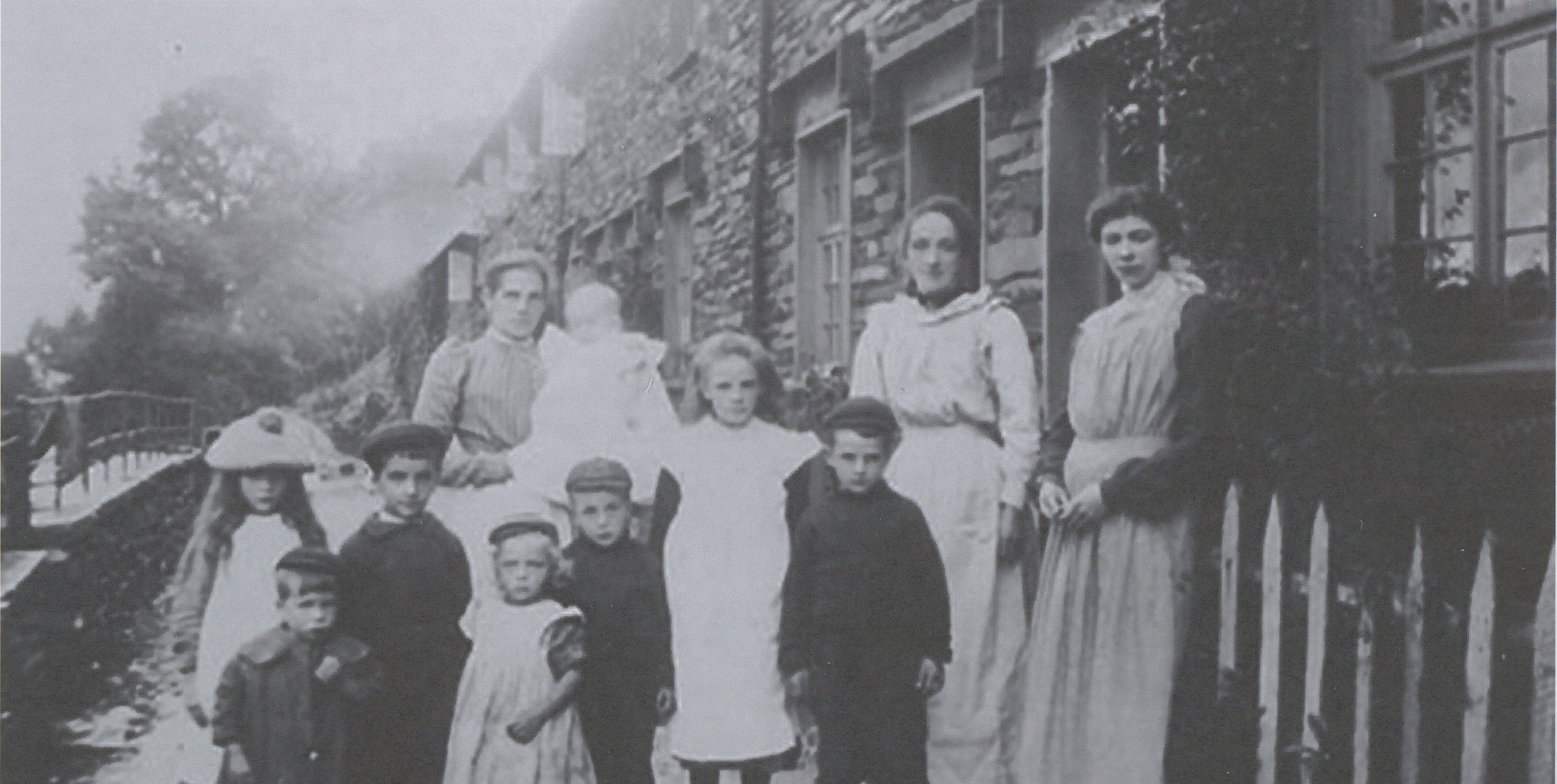 Historic photograph of residents outside Cat Bank, a terrace built for miners by the Coniston Copper Mine company.