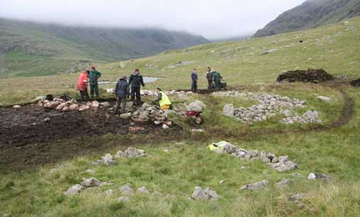 Seathwaite Ring cairn with large one being de-turfed