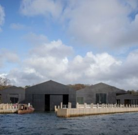 A view of teh new Windermere Jetty Museum taken from WIndermere with eth sjy in the background