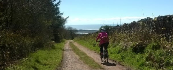 Connie on her ebike travelling along a path in the Western Lakes