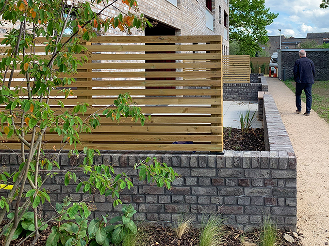 A slatted wooden fence on top of a low brick wall.