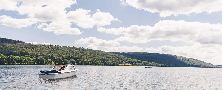 A family exploring Coniston Water by boat on a summer's day.