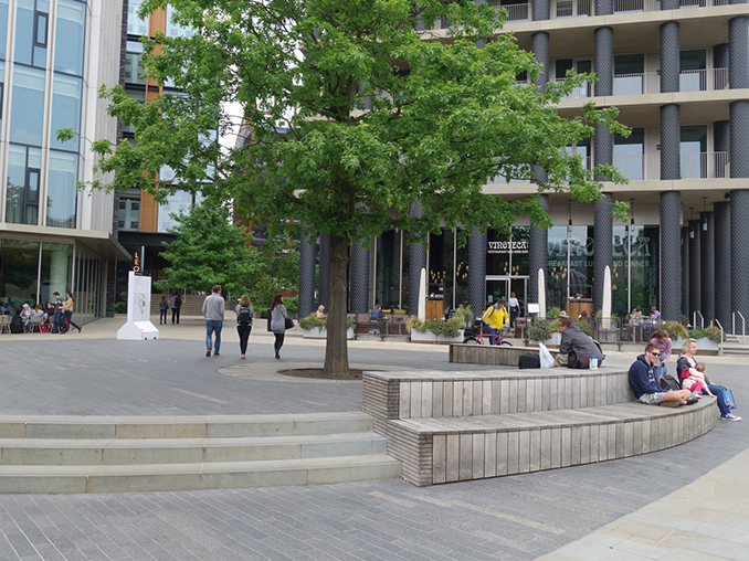 People sat on tiered seating around a tree outside a rail station.