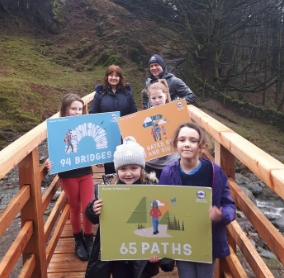 Lake District National Park Chief Executive Richard Leafe and Jacquie Middleton from the Rural Payments Agency alongside some local youngsters who helped celebrate the completion of the Routes to Resilience Programme at Greenhead Gill Bridge in Grasmere.