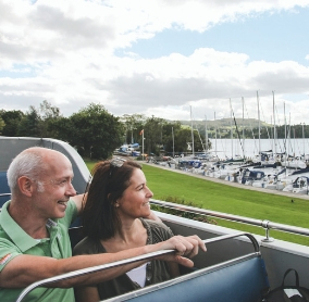 Couple aboard an open top but looking out ofver a lake and boats on a beautiful spring day
