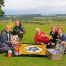 sitting on a picnic blanket is  David Bliss, Lowther Castle, Dylan Jackman, Ranger with Lake District National Park, Tim Clarke, Friends of the Ullswater Way, Suzy Hankin, Area Ranger with Lake District National Park and Anne Clarke, Friends of the Ullswater Way.