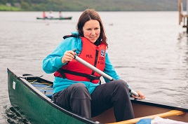 A visitor rowing on Coniston Water.%