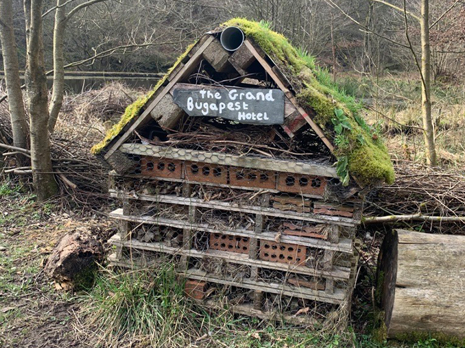 A bug hotel made of wooden palettes and bricks with a moss roof.