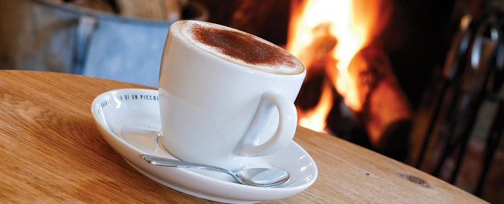 A big mug filled with hot chocolate next to a roaring fire