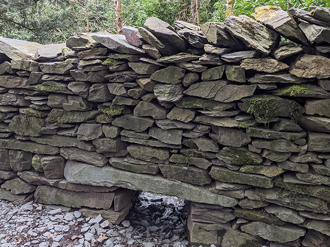 Dry stone wall with a small opening at ground level to allow water and wildlife to pass through.
