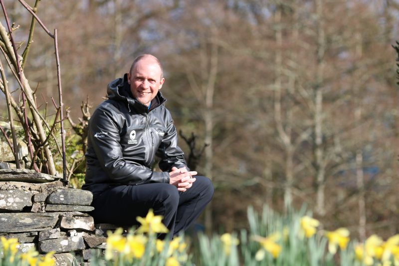 Richard Leafe Sat on a wall with Spring daffodils