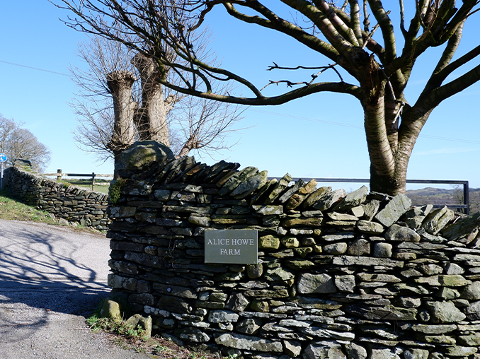 Dry stone wall at the entrance to a farm with a sign set into the wall.