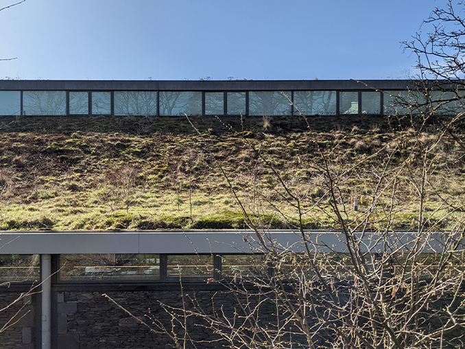 A moss and plant covered roof on a modern building.