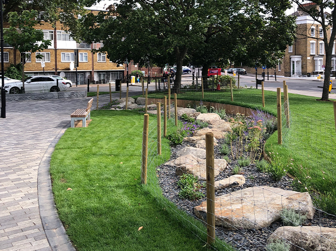 Large flat rocks amongst grass and tree planting next to a pathed walkway.