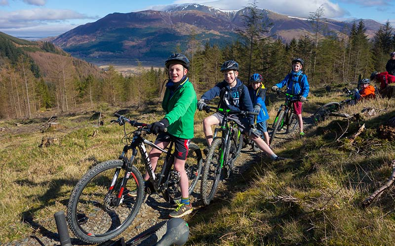 Children on mountain bikes on a fellside in the Lake District