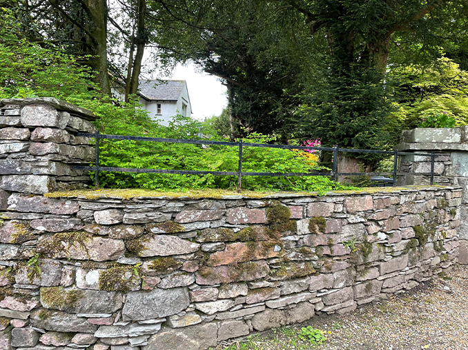 Stone wall with metal railings above.