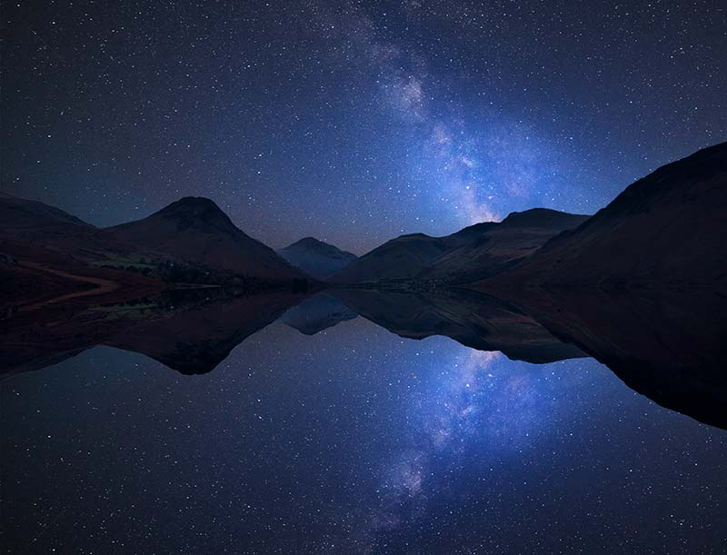 Dark Starry skies above mountains reflected in a lake below
