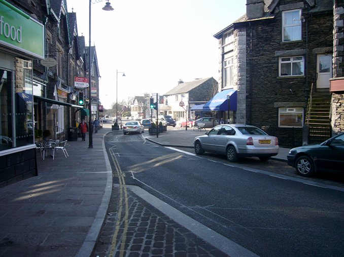Cars parked on town street with wide pavement next to a cafe.