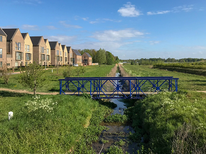 A bridge over a stream with the path leading to a housing estate.