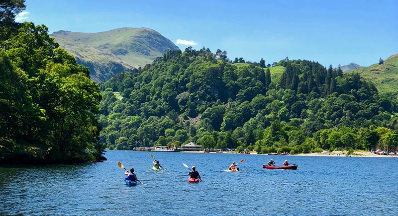 Kayaking on Ullswater lake with mountains in the background