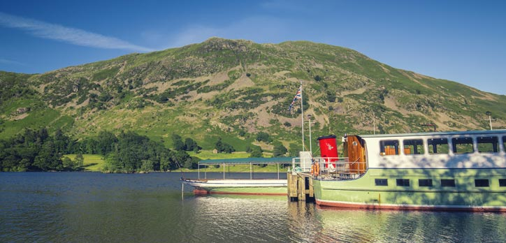 A steam boat floating on a lake in the Lake District.