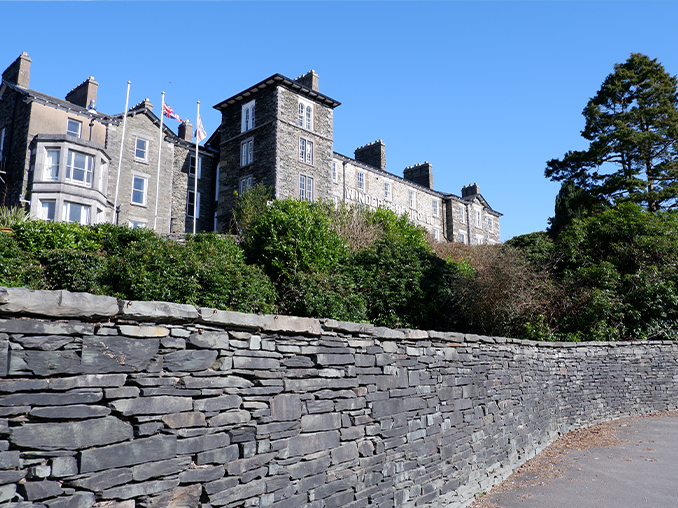 A stone wall with a stone built hotel behind.