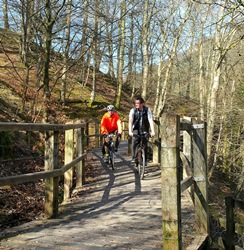 Photo 2 shows: cyclists enjoy the raised boardwalk section of the Keswick to Threlkeld Railway Path, which reopened on 18 March following the December floods.