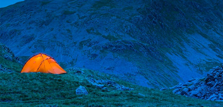 A bright orange tent wild camping on a dark mountainside