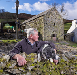 Farmer and sheepdog outside a restored barn