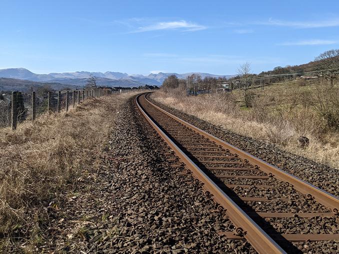Railway line with fells on the horizon.