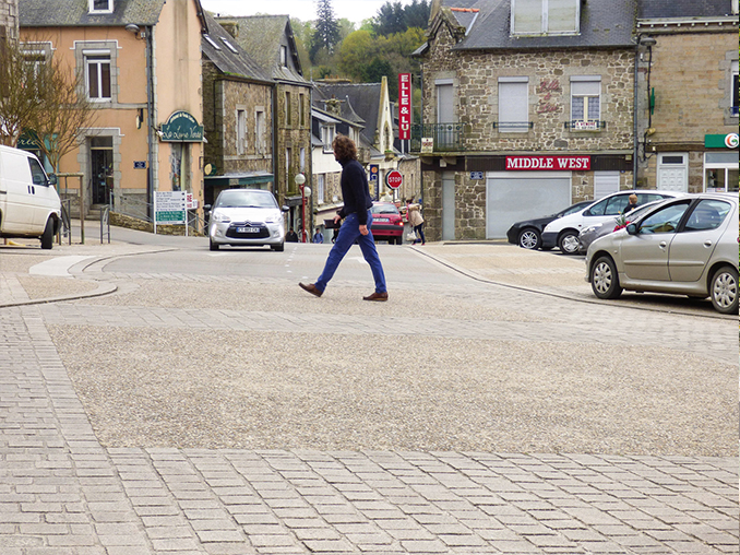 Cobbled area across a road in a village in France.