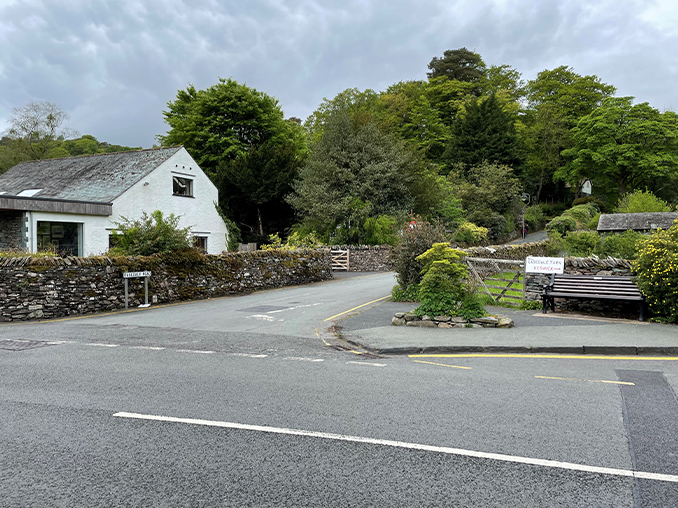 Road junction with signs set into stone wall.