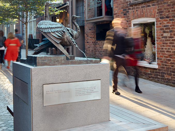 A statue and seating in a city street.