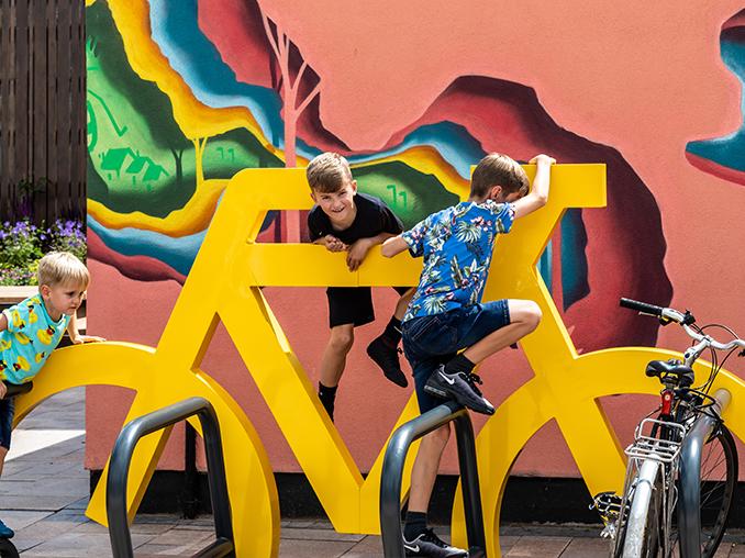 Children climbing on bicycle parking.
