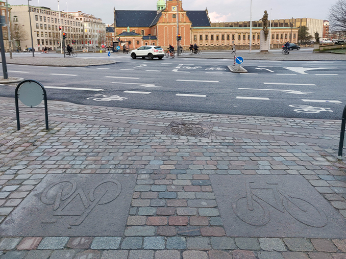 Cobbled street surface with a bicycle symbol laid in stone.